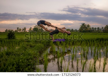 outdoors sunset acroyoga workout silhouette- young happy and fit couple practicing acro yoga drill at beautiful rice field enjoying nature and healthy lifestyle doing acrobatic pose  #1712526073