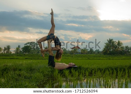 outdoors sunset acroyoga workout - young happy and fit couple practicing acro yoga drill at beautiful rice field enjoying nature and healthy lifestyle doing acrobatic pose  #1712526094
