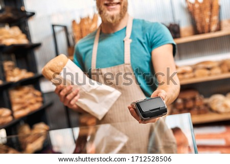 Young bearded man wearing eyeglasses and apron assistant standing at bakery shop small business giving card reader machine to customer taking payment for bread loaf close-up smiling happy