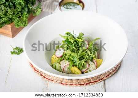 Salad with potatoes, radishes, fresh herbs in a white plate #1712534830