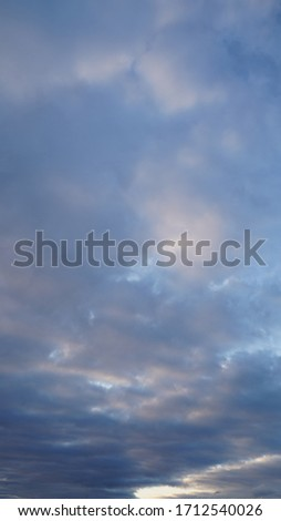A beautiful evening blue sky at sunset with flaming bright light clouds. Warm evening. #1712540026