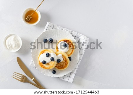 Cottage cheese pancakes on a white background. Syrniki with fresh blueberries. Pancakes with cottage cheese on a white board sprinkled with powdered sugar. Homemade food. Recipe. Copy space for text #1712544463