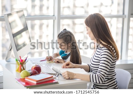 Homework. Dark-haired girl and her tutor sitting at the table doing homework #1712545756