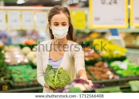 shopping, food, sale, consumerism and people concept - happy woman in face protective medical mask for protection from virus disease buying savoy at grocery store or supermarket #1712566408