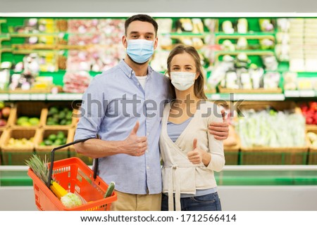 shopping, sale, consumerism and people concept - happy couple wearing face protective medical masks for protection from virus disease with food basket at grocery store or supermarket showing thumbs up #1712566414
