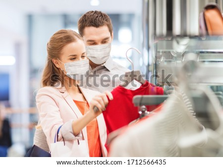 sale, consumerism and pandemic concept - happy young couple wearing face protective medical mask for protection from virus disease with shopping bags in mall #1712566435