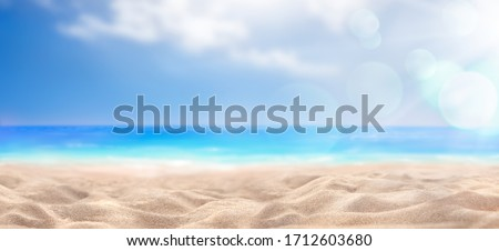 A summer vacation, holiday background of a tropical beach and blue sea and white clouds with sun flare.
