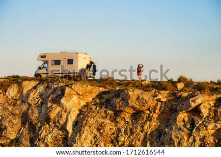 Female traveling with motor home. Camper vehicle wild camping on cliff rock, Cabo de Gata Nijar Natural Park in Almeria province, Andalusia Spain. #1712616544