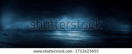 Dark street, wet asphalt, reflections of rays in the water. Abstract dark blue background, smoke, smog. Empty dark scene, neon light, spotlights. Concrete floor #1712623603