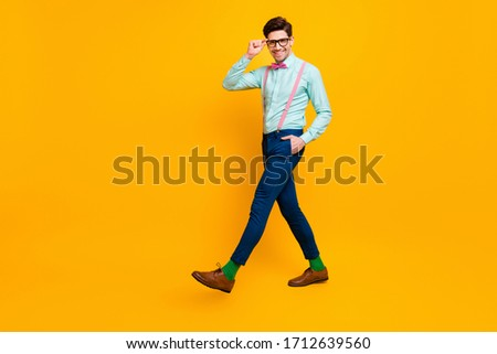 Full size profile photo of cool stylish guy boyfriend walk down street date girlfriend wear specs shirt bow tie suspenders trousers shoes isolated bright yellow color background #1712639560