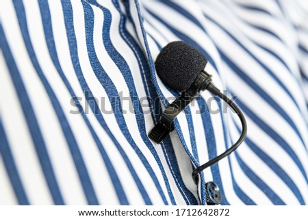 Black Clip-On Microphone on a blue striped shirt