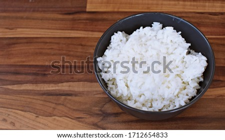 A bowl full of cooked white rice stands on a dark background - delicious, healthy, fresh rice with space for text or other elements next to it #1712654833