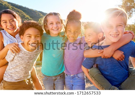 Portrait Of Multi-Cultural Children Hanging Out With Friends In Countryside Together #1712657533