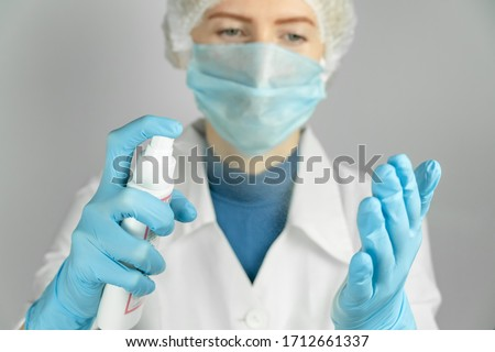 Doctor in a white coat, medical mask, medical cap and blue gloves disinfects his hands with antiseptic spray close-up #1712661337