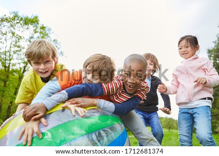 Multicultural kids group has fun playing ball in the park in kindergarten #1712681374