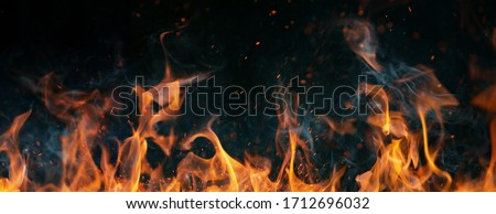 Closeup of fire isolated on black background Royalty-Free Stock Photo #1712696032
