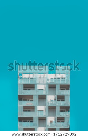 Architectural detail of a residential building with modern and playful glass facade against clear, blue sky. Architectural photography. Minimal aesthetics.