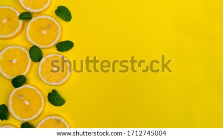 Lemon slices and fresh green mint leaves, on a yellow background. Juicy food pattern. Empty space. Flat lay, top view. Stylized photo. #1712745004