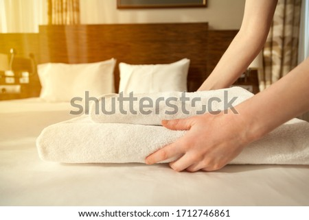 photo close up of hands putting stack-of fresh white bath towels on the bed-sheet room service maid #1712746861
