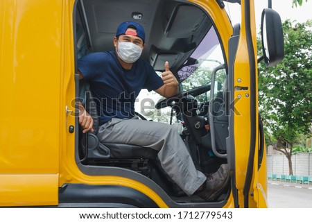 Photos of Asian truck drivers wearing masks to protect against dust and the spread of COVID 19 in front of the car. Safety ideas for a worker in the transportation business. And is a new normal life. #1712779543