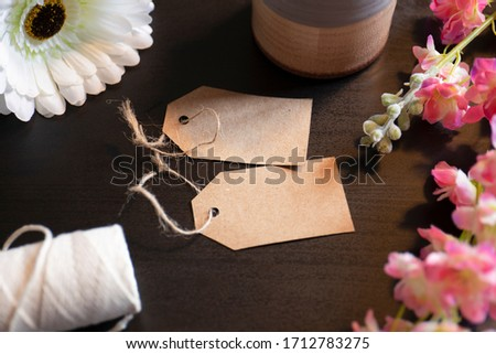 This high resolution Tags Label Stock Photo on Dark Wood Table and Flowers can be used as a beautiful retro mock-up to help visualize your products, or simply as a nice vintage background image.
