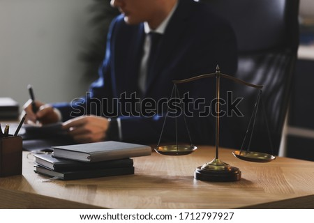 Male lawyer working at table in office, focus on scales of justice #1712797927