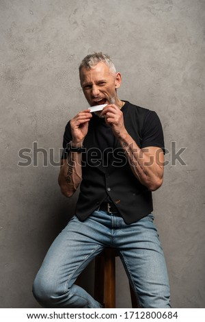 handsome man with tattoos biting blank card on grey