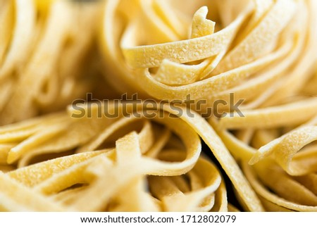 Macro picture of traditional Italian raw pasta Tagliatelle, selective focus image. Vegeterian food. Nutrition concept. Italian kitchen. Food preparation. Food pasta background. Wallpaper. Tasty.