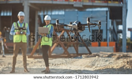 Diverse Team of Specialists Pilot Drone on Construction Site. Architectural Engineer and Safety Engineering Inspector Fly Drone on Commercial Building Construction Site Controlling Design and Quality #1712803942