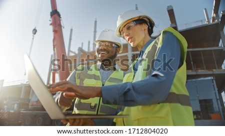 Two Specialists Inspect Commercial, Industrial Building Construction Site. Real Estate Project with Civil Engineer, Investor Use Laptop. In the Background Crane, Skyscraper Concrete Formwork Frames Royalty-Free Stock Photo #1712804020