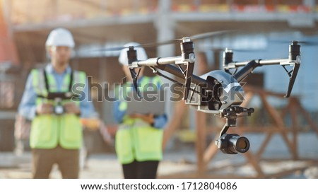 Two Specialists Use Drone on Construction Site. Architectural Engineer and Safety Engineering Inspector Fly Drone on Building Construction Site Controlling Quality. Focus on Drone #1712804086
