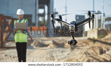 Specialist Controlling Drone on Construction Site. Architectural Engineer or Inspector Fly Drone on Building Construction Site Controlling Quality. Focus on Drone #1712804092