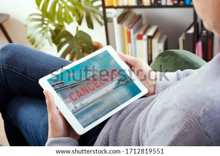 closeup of a young caucasian man, lying comfortably on an armchair, watching his tablet, with a picture of a cruise ship and the text cancelled in its screen, depicting the cancellation of a trip