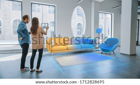 Decorating Apartment: Lovely Young Couple Use Digital Tablet with Augmented Reality Interior Design Software to Choose 3D Furniture for their Home. People Pick Sofa, Table and Lighting for Living Room #1712828695