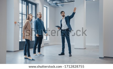 Real Estate Agent Showing a New Empty Office Space to Young Male and Female Hipsters. Entrepreneurs Meet the Broker with a Tablet and Discuss the Facility They Wish to Purchase or Rent. #1712828755