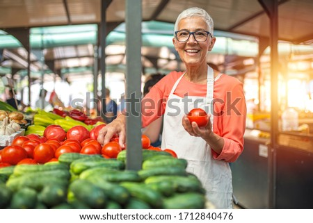 Woman tending an organic vegetable stall at a farmer's market and selling fresh vegetables. Female gardener selling organic crops and picking up a bountiful basket full of fresh produce. Only organic. #1712840476