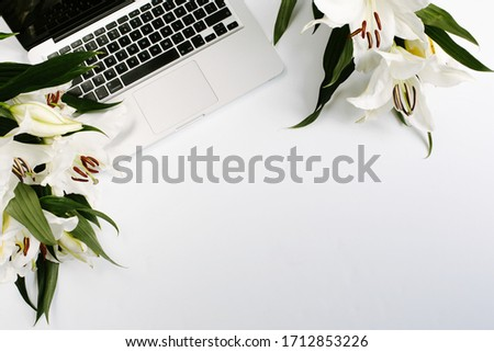 Keyboard of a laptop with green flowers on white background. Mockup with copyspace in flat lay style. #1712853226