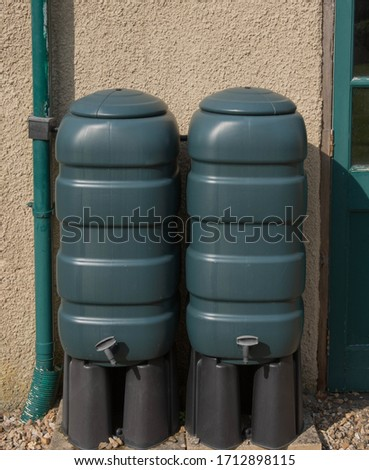 Two Green Plastic Water Butts Connected to a Down Pipe Collecting Rain Water in a Country Cottage Garden in Rural Devon, England, UK #1712898115