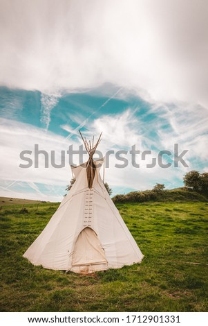 Native American tent on a green field with blue sky Vertical