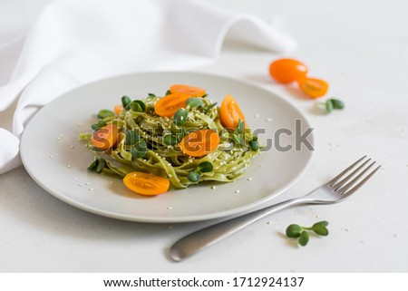 Green vegan healthy pasta with orange tomatoes and micro greens with white towel on the background and fork  #1712924137