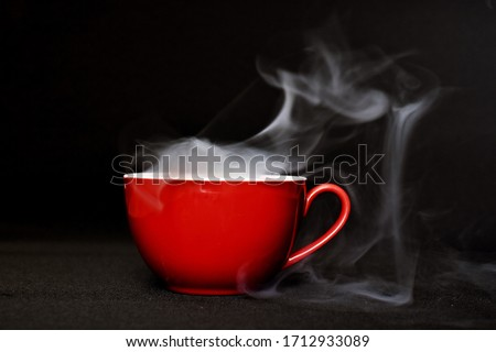 A cup full of smoke stands on a black surface with strong contrasts - smoke holds in a cup stands in front of a black background - mystical and dark picture with smoke and cup