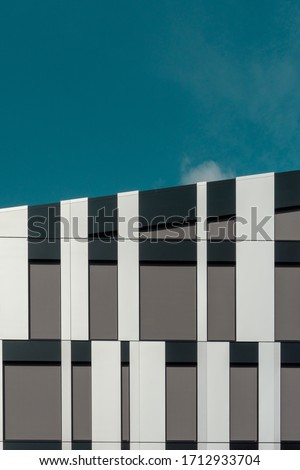 Detail of a modern office building with decorative facade cladding panels. Architecture photography. Copy space.