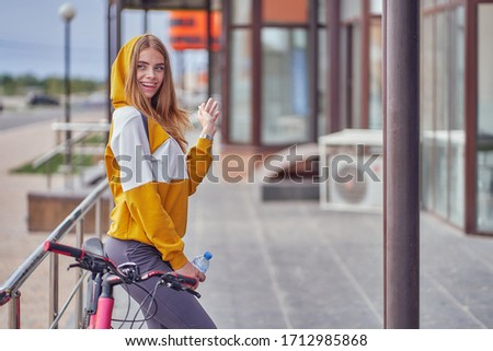 A young girl smiles while sitting on a bicycle and holds a water bottle in her hands. #1712985868