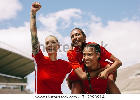 Excited female soccer players celebrating after scoring a goal. Teammates celebrating victory holding the goal scorer. Royalty-Free Stock Photo #1712993914