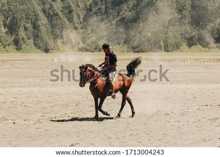 Bromo, Indonesia - July 24, 2016: The men ride a horse (horsemen) in the desert (Bromo Tengger Semeru National Park) #1713004243