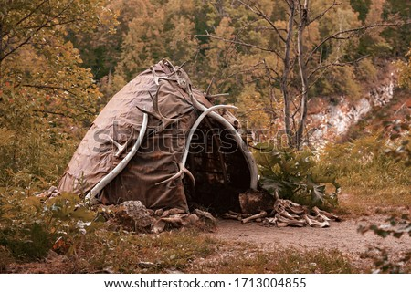 Hut of ancient people. Prehistoric dwelling place, primitive architecture. Wigwam made of animal skins surrounded with mammoth tusks. The cabin of an ancient man. Leathers shelter of primitive man #1713004855