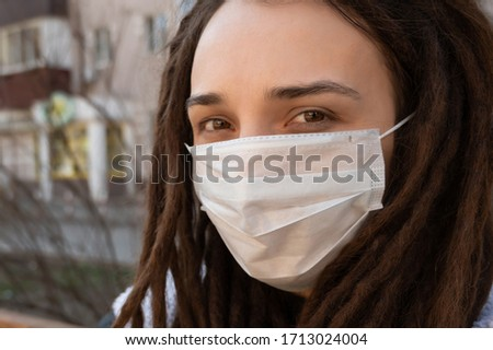 beautiful young girl wearing medical mask in a public place #1713024004