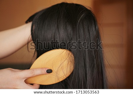 Female hand holds a black wig with long hair and combs a wooden comb. Hairdresser and hair care Royalty-Free Stock Photo #1713053563