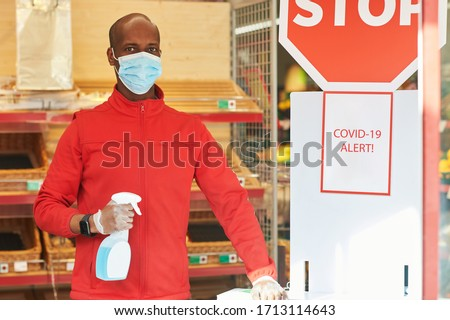 Shop employee at the entrance of the supermarket spraying disinfectant on customers hands for safety measures during covid-19 #1713114643