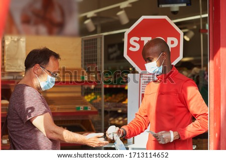Shop employee at the entrance of the supermarket spraying disinfectant on customers hands for safety measures during covid-19 Royalty-Free Stock Photo #1713114652